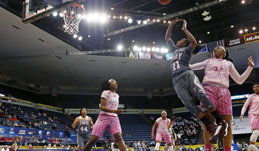 Troy guard ArJae' Saunders (11) shoots between Louisiana-Lafayette forward Simone Fields (32) and guard/forward Gabby Alexander (22) during the first half of an NCAA college basketball game for the Sun Belt tournament title in New Orleans, Sunday, March 12, 2017.  (AP Photo/Gerald Herbert)