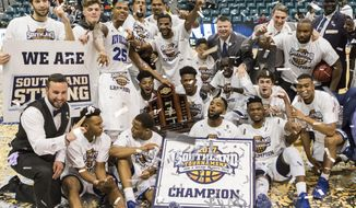 New Orleans team member celebrate at midcourt with the championship trophy after New Orleans defeated Texas A&M-Corpus Christi 68-65 in overtime in an NCAA college basketball game for the championship of the Southland Conference tournament Saturday, March 11, 2017, in Katy, Texas. (AP Photo/Joe Buvid)