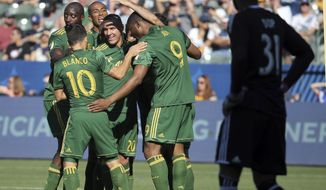 Portland Timbers celebrate a goal against LA Galaxy goalkeeper Clement Diop, right, in the first half of an MLS soccer match in Carson, Calif., Sunday, March 12, 2017. (AP Photo/Reed Saxon)