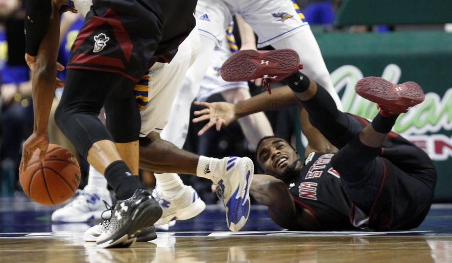 New Mexico State guard Ian Baker (4) tumbles onto the court after chasing a loose ball during the first half of an NCAA college basketball game against Cal State Bakersfield in the final of the Western Athletic Conference tournament Saturday, March 11, 2017, in Las Vegas. (AP Photo/L.E. Baskow)