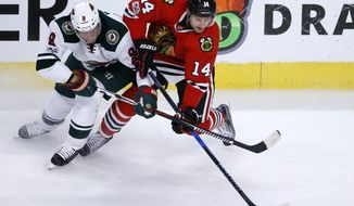Chicago Blackhawks' Richard Panik (14) and Minnesota Wild's Mikko Koivu battle for the puck during the first period of an NHL hockey game Sunday, March 12, 2017, in Chicago. (AP Photo/Charles Rex Arbogast)
