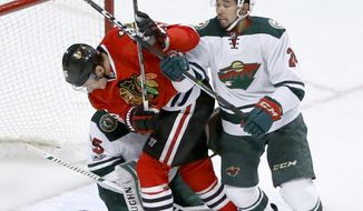 Minnesota Wild's Matt Dumba (24) pushes Chicago Blackhawks' Artem Anisimov (15) across Wild goalie Darcy Kuemper during the first period of an NHL hockey game Sunday, March 12, 2017, in Chicago. (AP Photo/Charles Rex Arbogast)