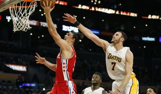 Philadelphia 76ers forward Dario Saric, left, scores in front of Los Angeles Lakers forward Larry Nance Jr., right, during the second half of an NBA basketball game, Sunday, March 12, 2017, in Los Angeles. The 76ers won 118-116. (AP Photo/Danny Moloshok)