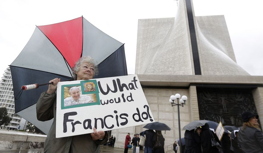 Marti Kashuba holds up a sign outside of St. Mary's Cathedral in San Francisco, Friday, Feb. 6, 2015. The Roman Catholic archbishop of San Francisco is getting pushback from some parents, students and teachers at parochial schools after unveiling faculty handbook language calling on teachers to lead their public and professional lives consistently with church teachings on homosexuality, same-sex marriage, abortion, birth control and other behaviors he describes as evil.  (AP Photo/Jeff Chiu) **FILE**