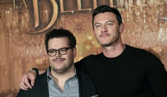 """In this Feb. 20, 2017, file photo, actor Josh Gad, left, who plays manservant LeFou and Luke Evans who plays villain Gaston, pose during a promotional event for the movie """"Beauty and the Beast,"""" in Paris. Walt Disney has shelved the release of its new movie """"Beauty and the Beast"""" in mainly Muslim Malaysia, even though film censors said Tuesday, March 14, 2017, it had been approved with a minor cut involving a """"gay moment"""" between two characters in the film. (AP Photo/Christophe Ena, File)"""