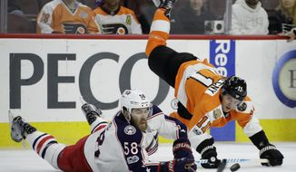 Columbus Blue Jackets' David Savard (58) and Philadelphia Flyers' Travis Konecny (11) dive for a loose puck during the first period of an NHL hockey game, Monday, March 13, 2017, in Philadelphia. (AP Photo/Matt Slocum)