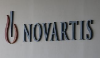 FILE - In a Saturday, Aug. 13, 2016 file photo, logo of Swiss pharmaceutical company Novartis is seen at the Novartis Korea office in Seoul, South Korea. U.S. regulators have approved a new drug as an initial treatment for postmenopausal women with a type of advanced breast cancer. The drug, called Kisqali, developed by Swiss drugmaker Novartis, is a pill that works to slow the spread of cancer by blocking two proteins that can stimulate growth and division of cancer cells. (AP Photo/Ahn Young-joon, File)