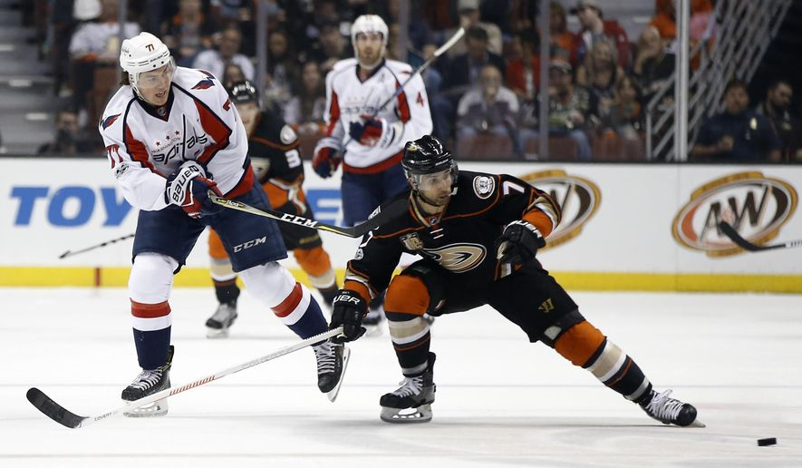 Washington Capitals right wing T.J. Oshie (77) passes the puck past Anaheim Ducks left wing Andrew Cogliano (7) during the first period of an NHL hockey game in Anaheim, Calif., Sunday, March 12, 2017. (AP Photo/Alex Gallardo)