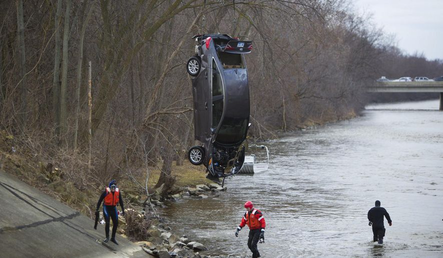 Crews work to remove a Hyundai Sonata that crashed into the Kalamazoo River in Battle Creek more than a week ago from the Kalamazoo River on Sunday, March 12, 2017, in Battle Creek, Mich. Police say they were told a 31-year-old man may have been driving the car, but a body wasn't found with the vehicle. A search for the man will continue. (Carly Geraci/Kalamazoo Gazette-MLive Media Group via AP)