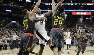San Antonio Spurs forward Kawhi Leonard (2) drives to the basket against Atlanta Hawks defenders Thabo Sefolosha (25) and Kent Bazemore (24) during the first half of an NBA basketball game, Monday, March 13, 2017, in San Antonio. (AP Photo/Eric Gay)