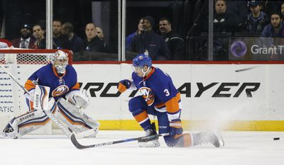 New York Islanders defenseman Travis Hamonic (3) tries to block a shot as New York Islanders goalie Thomas Greiss (1), of Germany, keeps his eyes on the puck during the second period of an NHL hockey game against the Carolina Hurricanes, Monday, March 13, 2017, in New York, (AP Photo/Kathy Willens)
