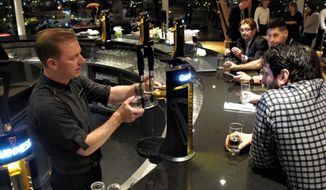 Guinness beer expert Domhnall Marnell pours visitors a pint of stout during an advance preview of the Gravity Bar penthouse layout in Dublin, Ireland, on Tuesday, March 7, 2017. (AP Photo/Shawn Pogatchnik) ** FILE **