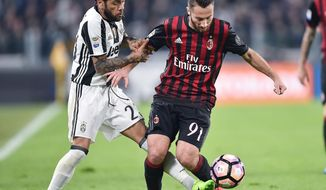 Juventus' Dani Alves, left, and Milan's Andrea Bertolacci vie for the ball during the Italian Serie A soccer match between Juventus and Milan at the Juventus stadium in Turin, Italy, Friday, March 10, 2017. (Alessandro Di Marco/ANSA via AP)