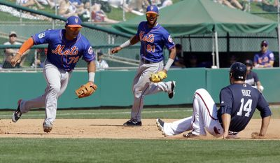 New York Mets third baseman Phillip Evans (72) runs to tag out Atlanta Braves' Rio Ruiz (14) after he was caught off-base on a fielder's choice play as shortstop Amed Rosario (61) looks on in the fifth inning of a spring training baseball game, Friday, March 10, 2017, in Kissimmee, Fla. (AP Photo/John Raoux)