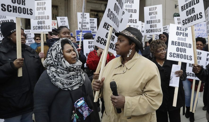 In this Friday, Feb. 17, 2017, photo, Roquesha O'Neal, left, and Shoniqua Kemp participate in a rally in Detroit. Dozens protested Michigan's threat to close dozens of underperforming public schools in Detroit and several other cities. The plan is angering parents and frustrating educators faced with limited options to provide better learning. (AP Photo/Carlos Osorio)