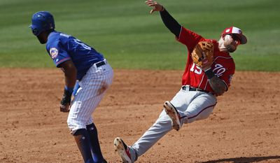 Washington Nationals second baseman Brandon Synder (19) falls backwards after forcing out New York Mets' Amed Rosario (61) on a ground ball by Wuilmer Becerra in the fifth inning of a spring training baseball game, Saturday, March 11, 2017, in Port St. Lucie, Fla. (AP Photo/John Bazemore)