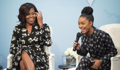 """FILE - In this Oct. 11, 2016, file photo, first lady Michelle Obama laughs with actress Yara Shahidi while participating in Glamour's """"A Brighter Future: A Global Conversation on Girls' Education,"""" in celebration of International Day of the Girl and Let Girls Learn at the Newseum in Washington. Shahidi tells W magazine for an article published online on March 13, 2017, that Obama wrote her a college recommendation letter. (AP Photo/Molly Riley, File)"""