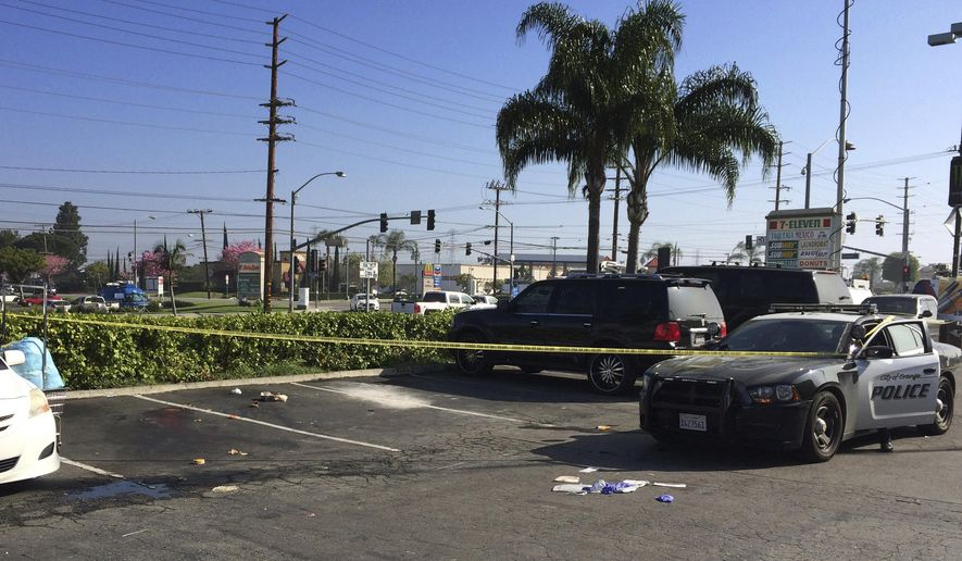 A police car is parked in a parking lot on Monday, March 13, 2017, next to yellow police tape where an officer involved shooting took place on Sunday. California police shot a man dead after he barricaded himself inside a minivan with gas can and a lighter during a traffic stop before emerging with a knife, officials said Monday. Officers in the Los Angeles suburb of Orange pulled over the white minivan late Sunday for a vehicle code violation when the driver shut himself inside with a cigarette and lighter and poured gasoline onto a rag, said Orange police Lt. Fred Lopez. (AP Photo/Amy Taxin)