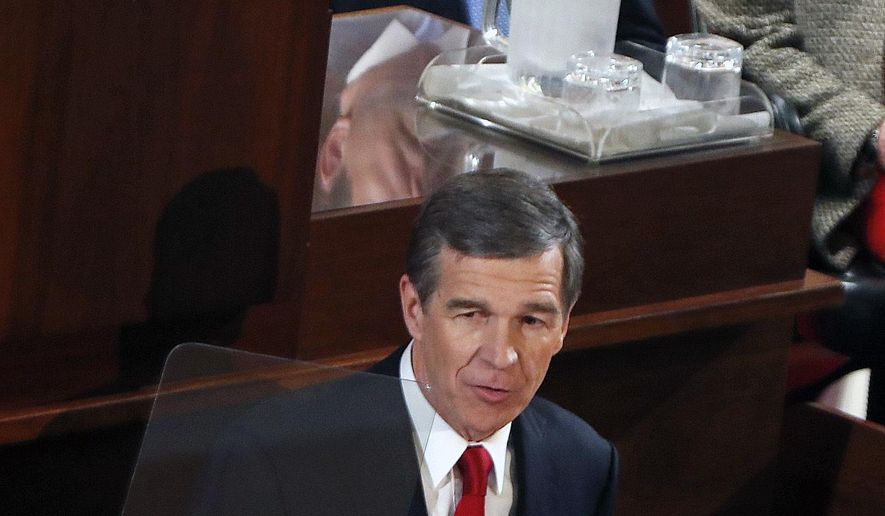 Gov. Roy Cooper, foreground,, asks the lawmakers to repeal HB2 as he delivers his first State of the State address to a joint session of the state legislature in the House chamber of the Legislative Building in Raleigh, N.C., Monday, March 13, 2017. Sen. Phil Berger, president pro tem, top, looks on. (Chris Seward/The News & Observer via AP)