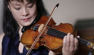 FILE - In this March 8, 2017, file photo, violinist Mira Wang plays the Ames Stradivarius violin in New York. After a meticulous restoration that took more than a year, the Stradivarius violin that was stolen from violinist Roman Totenberg is about to return to the stage. Wang, a former student of Totenberg's, will play the instrument at a private concert in New York on Monday, March 13, 2017. (AP Photo/Seth Wenig, File)