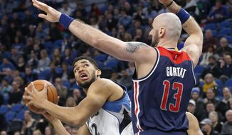 Minnesota Timberwolves' Karl-Anthony Towns, left, eyes the basket as Washington Wizards' Marcin Gortat, of Poland, defends during the first half of an NBA basketball game, Monday, March 13, 2017, in Minneapolis. (AP Photo/Jim Mone)