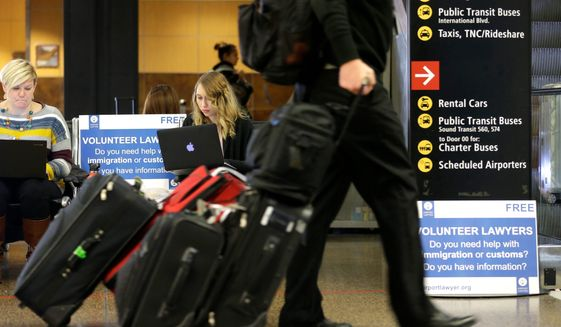 Travelers have been assured that legal residents of the United States will not be barred from re-entering the country under the terms of President Trump's newest travel ban. (Associated Press) ** FILE **