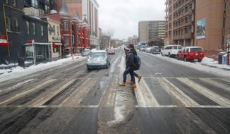 Pedestrians use the crosswalk at U Street in lighter than normal traffic in the District on Tuesday. A storm of snow and freezing rain covered most of the region. (Associated Press)