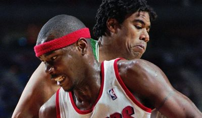 """FILE - In this Dec. 27, 1995, file photo, Portland Trail Blazers forward Cliff Robinson, front, drives on Boston Celtics' Pervis Ellison during NBA action in Portland, Ore. Former Trail Blazer Robinson says he is recovering from a """"minor brain hemorrhage."""" Last week Robinson's family disclosed that the 50-year-old former forward was being treated at Providence St. Vincent Medical Center. Robinson issued a statement on Tuesday, March 14, 2017, saying he's in the """"process of getting better."""" (AP Photo/Don Ryan, File)"""