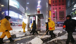 A crew of snow shovelers work as a snowstorm sweeps through Times Square, Tuesday, March 14, 2017, in New York. (AP Photo/Mark Lennihan)