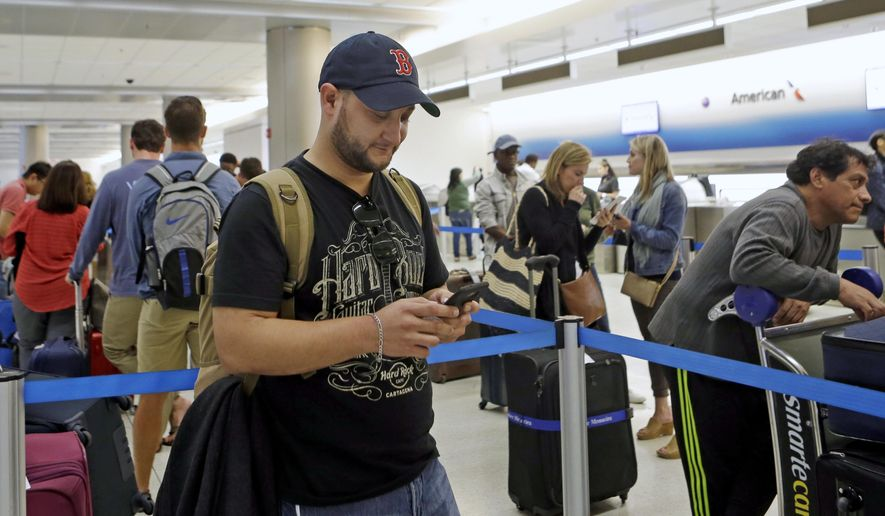 Airline passenger Carlos Sierra, of Honduras, checks the weather on his mobile phone as he waits to rebook his connection flight to Providence, R.I., at the American Airlines counter at Miami International Airport Monday, March 13, 2017, in Miami. (AP Photo/Alan Diaz)