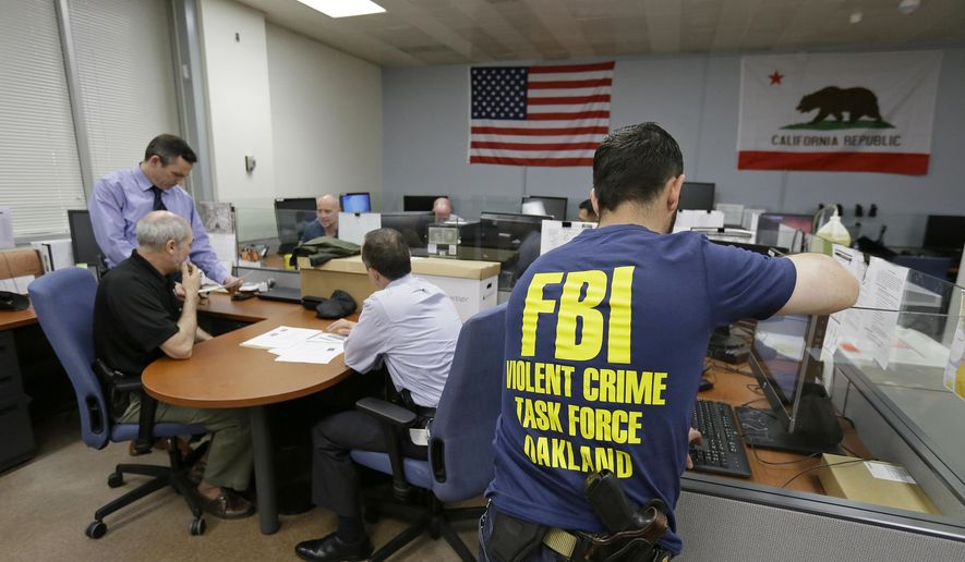 In this Friday, March 10, 2017, photo, Oakland police detectives and FBI agents work together in the offices of the Oakland Safe Streets Task Force in Oakland, Calif. Standing at left is Oakland homicide detective Jason Turner. The federal government already plays a big role in fighting violent crime in cities, through grants and partnerships. Ten FBI agents now share an office with Oakland detectives, offering help gathering evidence, collecting DNA, chasing leads and bringing federal prosecutions that carry longer sentences in far-away prisons. (AP Photo/Eric Risberg)