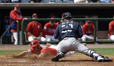 Philadelphia Phillies' Taylor Featherston, left, slides past Atlanta Braves catcher Anthony Recker to score a run in the fifth inning in a spring training baseball game, Tuesday, March 14, 2017, in Clearwater, Fla. (AP Photo/John Raoux)