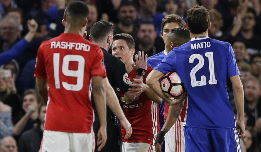 Manchester United's Ander Herrera, centre, argues with referee Michael Oliver, second left, after he was given a red card and sent him off during the English FA Cup quarterfinal soccer match between Chelsea and Manchester United at Stamford Bridge stadium in London, Monday, March 13, 2017 (AP Photo/Alastair Grant)