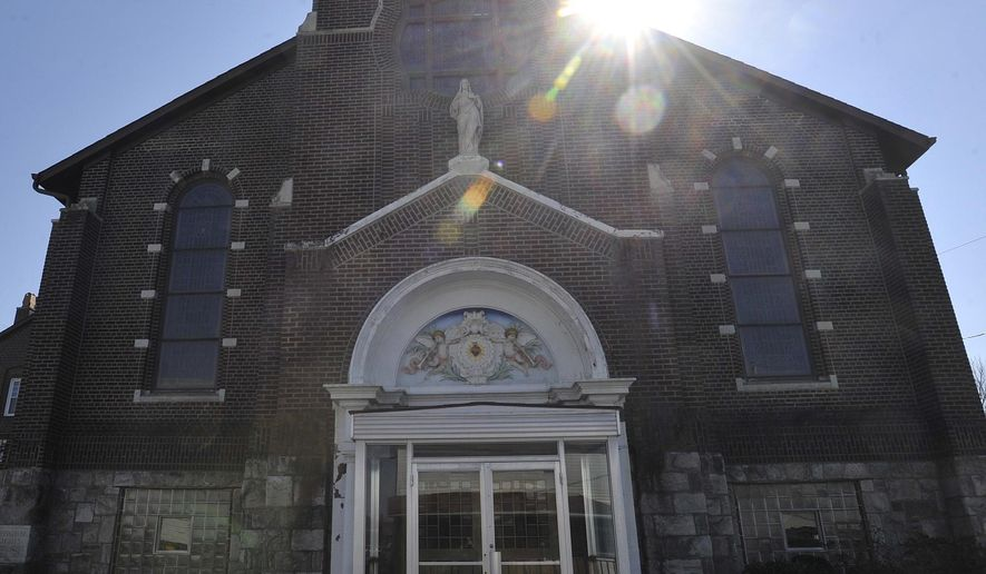 The sun rises behind the former Sacred Heart of Jesus Church in Portage, Pa., Thursday, March 9, 2017.  Facing a growing number of vacant, neglected structures, Portage Borough Council has taken an unusual approach for encouraging reuse of several former church properties. Council voted  to explore revoking tax-exempt status for the former Our Lady of the Sacred Heart Parish church buildings and a former church school. (Todd Berkey /The Tribune-Democrat via AP)
