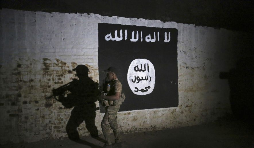 In this March 1, 2017 file photo, an Iraqi soldier inspects a recently-discovered train tunnel, adorned with an Islamic State group flag, that belonged to the former Baghdad to Mosul line, that was turned it to a training camp for IS fighters, in western Mosul, Iraq. (AP Photo/Khalid Mohammed, File)