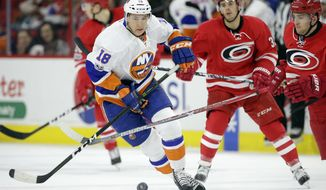 New York Islanders' Ryan Strome (18) chases the puck with Carolina Hurricanes' Noah Hanifin (5) and Derek Ryan, rear, during the first period of an NHL hockey game in Raleigh, N.C., Tuesday, March 14, 2017. (AP Photo/Gerry Broome)
