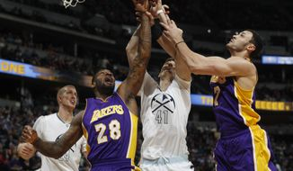 From left, Los Angeles Lakers center Tarik Black fights for a rebound with Denver Nuggets forward Juancho Hernangomez, of Spain, and Lakers forward Larry Nance Jr. in the first half of an NBA basketball game Monday, March 13, 2017, in Denver. (AP Photo/David Zalubowski)