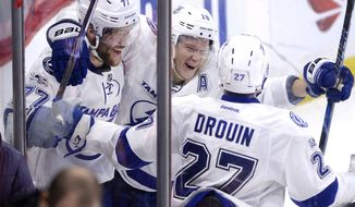 Tampa Bay Lightning's Victor Hedman (77) celebrates with teammates Ondrei Palat (18) and Jonathan Drouoin (27) after his game winning goal in overtime NHL hockey action against the Ottawa Senators, in Ottawa, Tuesday March 14, 2017. (Justin Tang/The Canadian Press via AP)