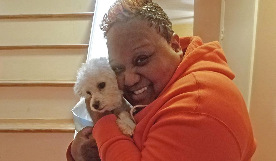 This Friday, March 3, 2017, photo provided by Tanya D. Flowers shows Flowers hugging her Maltese dog Paris after she was reunited with her dog at her apartment in Jersey City, N.J. An animal shelter in Staten Island, N.Y., called Flowers in early March 2017 to tell her Paris had been found after the dog disappeared in September 2016. (Tanya D. Flowers via AP)