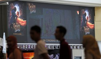 """People wait in queue to counter inside cinema at shopping mall in Kuala Lumpur, Malaysia on Tuesday, March 14, 2017. Walt Disney has shelved the release of its new movie """"Beauty and the Beast"""" in mainly Muslim Malaysia, even though film censors said Tuesday it had been approved with a minor cut involving a """"gay moment."""" (AP Photo/Daniel Chan)"""