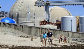 FILE - In this June 30, 2011 file photo, people walk on the sand near the shuttered San Onofre nuclear power plant in San Clemente, Calif. An arbitration panel on Monday, March 13, 2017 awarded Southern California utilities $125 million in a lawsuit claiming that Mitsubishi Heavy Industries supplied faulty steam generators that helped lead to the closure of the San Onofre plant. (AP Photo/Lenny Ignelzi, File)