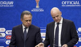 FILE - In this Nov. 26, 2016 file photo FIFA President Gianni Infantino, right, and Vitaly Mutko, Russia's deputy prime minister in charge of sport, tourism and youth policies, arrive for a news briefing ahead of the draw for the soccer Confederations Cup 2017, in Kazan, Russia. Russia World Cup head Mutko has been barred from seeking re-election to FIFA's top decision-making body after failing an eligibility check because of his role as a deputy prime minister of Russia.  (AP Photo/Ivan Sekretarev, file)