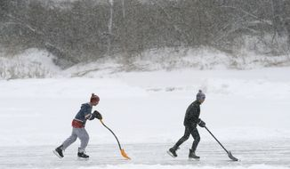 Pond hockey players attempt to shovel snow faster than it can fall during a storm, Tuesday, March 14, 2017, in Yarmouth, Maine. About one foot of snow is expected in the area. A blustery late-season storm is hitting the Northeast, closing schools and prompting dire warnings to stay off the roads. (AP Photo/Robert F. Bukaty)