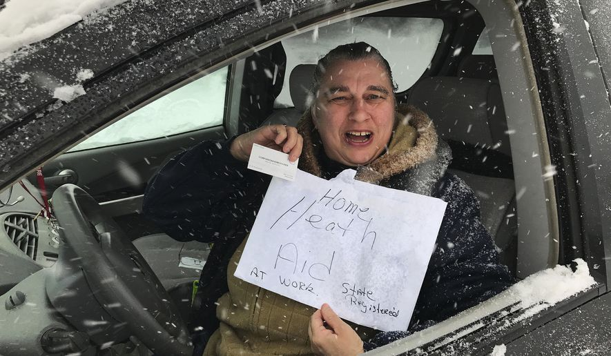 Home health care worker Nancy Ross holds up a sign while out during a late winter snow storm on Tuesday, March 14, 2017, in Bristol, Conn. (Mike Orazzi/The Bristol Press via AP)