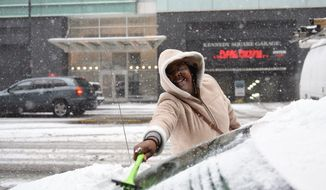 Haleema Russell cleans the snow off her car Monday, March 13, 2017, in Detroit. Two to three inches of snow areexpected to fall in southeast Michigan before midnight Monday. (Tanya Moutzalias/The Ann Arbor News-MLive.com Detroit via AP)