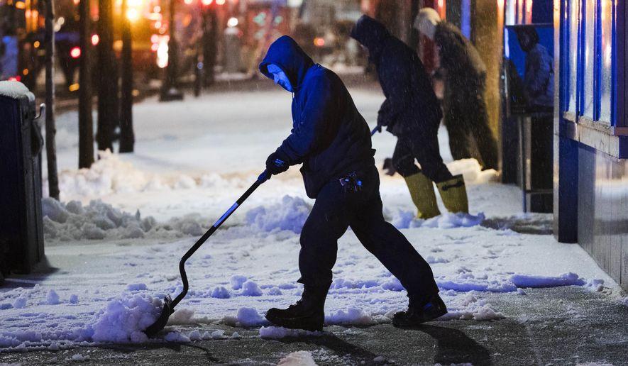 Workmen clear a sidewalk during a winter storm in Philadelphia, Tuesday, March 14, 2017. (AP Photo/Matt Rourke)