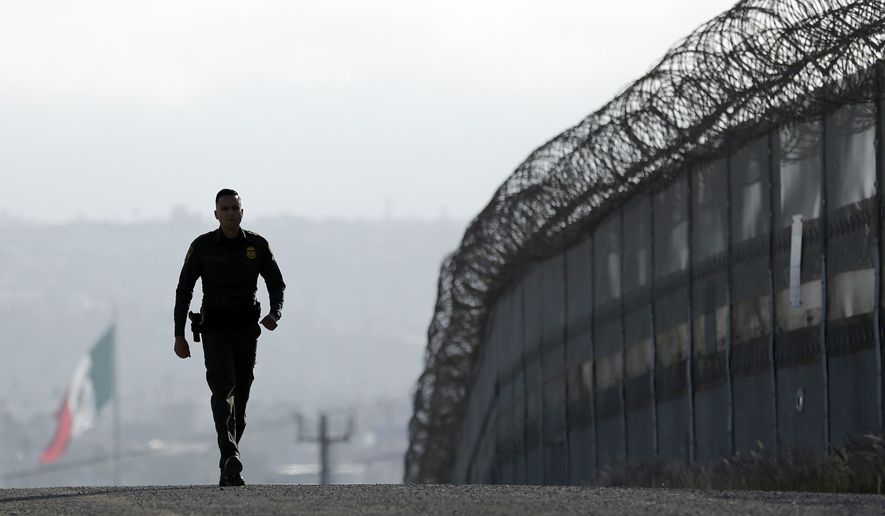 """Border Patrol agent Eduardo Olmos walks near the secondary fence separating Tijuana, Mexico, background, and San Diego in San Diego in June 2016. The Inter-American Commission on Human Rights, an arm of the Organization of American States, has said it will fight against President Trump's immigration plans. The group has accused him of fostering an """"enormous human rights crisis."""""""