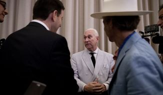 In this photo taken July 16, 2016, Roger Stone, an adviser to Donald Trump, center, speaks to reporters in New York. Stone says he believes his contacts with a Russian-linked hacker who took credit for breaching the Democratic National Committee were obtained through a FISA warrant, which allows the government to collect the communications of individuals suspected of being agents of a foreign power. (AP Photo/Mary Altaffer)
