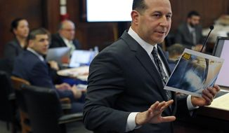 Jose Baez, defense attorney for defendant Aaron Hernandez, holds an evidence photo as he speaks to the jury during Hernandez's double murder trial in Suffolk Superior Court, Wednesday, March 15, 2017, in Boston. Hernandez is on trial for the July 2012 killings of Daniel de Abreu and Safiro Furtado who he encountered in a Boston nightclub. The former New England Patriots NFL football player is already serving a life sentence in the 2013 killing of semi-professional football player Odin Lloyd. (AP Photo/Elise Amendola, Pool)