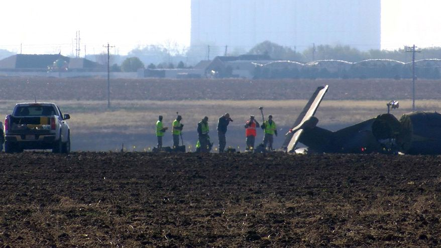 This frame grab from video supplied by KFDA-TV shows investigators looking over the broken fuselage of an Air Force plane Wednesday, March 15, 2017, in Clovis, N.M. The Air Force says three service members were killed when the single-engine reconnaissance and surveillance plane crashed in eastern New Mexico during a training flight. (KFDA-TV via AP)
